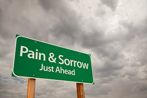 Pain and Sorrow Green Road Sign Over