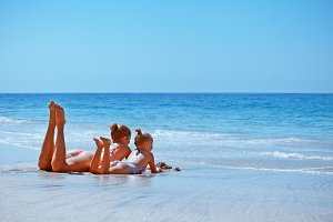 Child, mother relaxing on beach