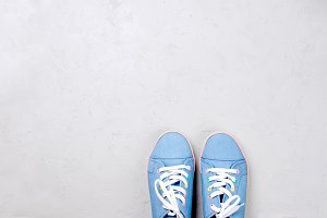 A pair of blue canvas sneakers on gr