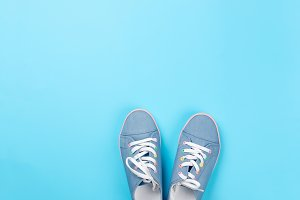 A pair of blue canvas sneakers on li