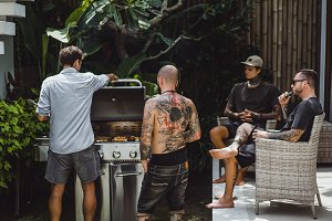 company of friends cooking barbecue