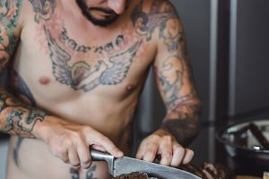 man in tattoos cuts meat