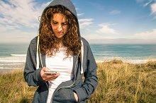 Woman with hoodie looking phone