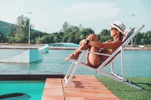 Young slim woman in bikini, straw ha