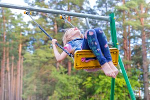 Pretty little blonde girl swinging o
