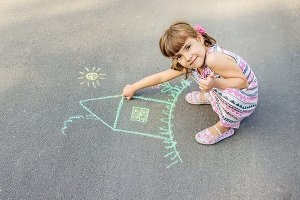 The child draws the house with chalk
