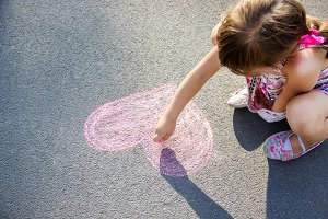 the child paints chalk on the asphal