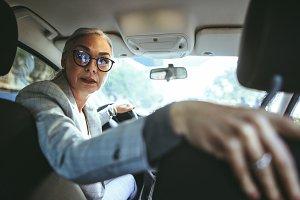 Senor woman driving a car in reverse