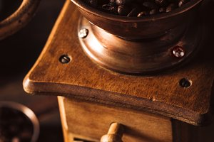 Old wooden coffee grinder with beans