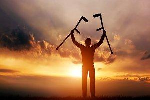 Man raising his crutches at sunset