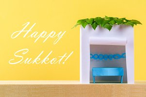 Text of Happy Sukkot. A hut made of
