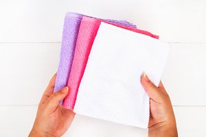 White, purple and pink towels in han