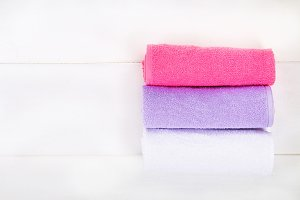 White, purple and pink towels on a w