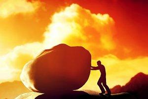 Man pushing a giant, heavy stone