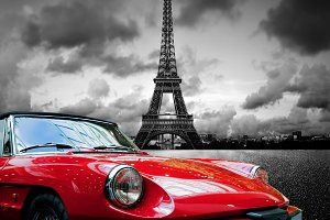 Red car next to the Eiffel Tower