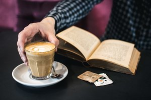 Reading book while drinking coffee