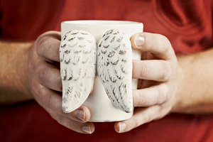 man's hand holding a cup of vintage