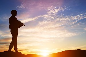 Armed soldier with rifle at sunset