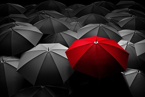 Red umbrella between black ones
