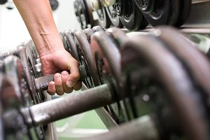 Man picking up dumbbells in a gym