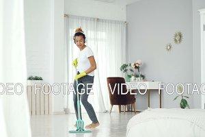 Happy housewife is doing housework