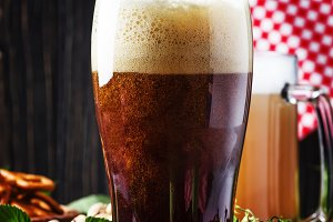 Dark German beer is poured into a gl