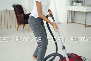 Active girl housewife is tidying