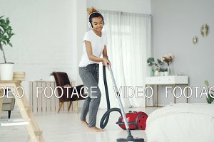 Cheerful housewife is using vacuum