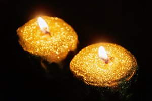 Close up of two lit gold candles on