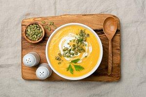 Pumpkin cream soup on wooden board