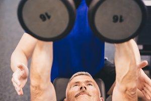 Senior man lifting weights assisted