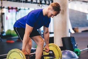 Muscular man lifting weights at the