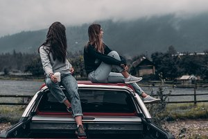 Two girls after a trip sit by car.