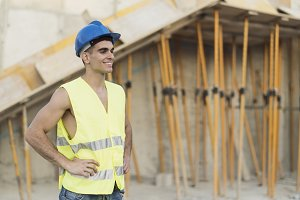 Smiling construction worker posing h