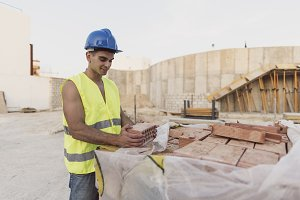 Young construction worker with brick