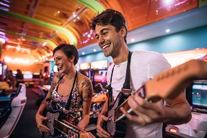 Happy couple playing a guitar arcade