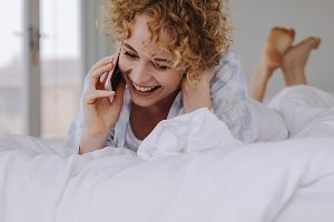 Smiling woman lying on bed talking