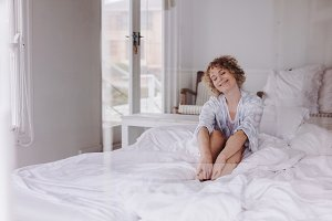 Smiling woman sitting on bed