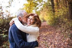 A senior couple hugging in an autumn