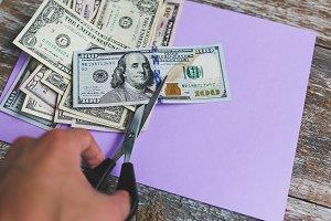 Man is cutting dollar banknotes