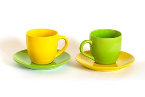 Two colored tea cups and saucers on