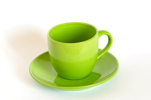Green tea cup and saucer on white ba