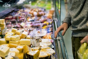 close up person choosing cheese in t