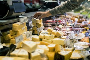 close up person hand buying cheese i