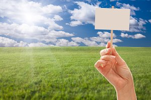 Blank Sign in Hand Over Grass Field
