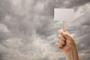 Man Holding Blank Sign Over Dark Sky
