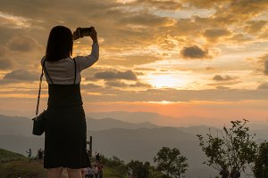 Woman taking photo in sunset.