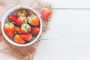 Fresh strawberries in bowl on wooden