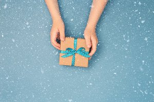 Childs hands holding one gift box