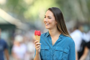 Woman holding an ice cream walking